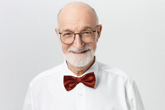 Image horizontale de succès beau mâle âgé barbu chauve vêtu de vêtements élégants posant au mur blanc, se réjouissant de bonnes nouvelles, à la recherche d'un sourire confiant rayonnant