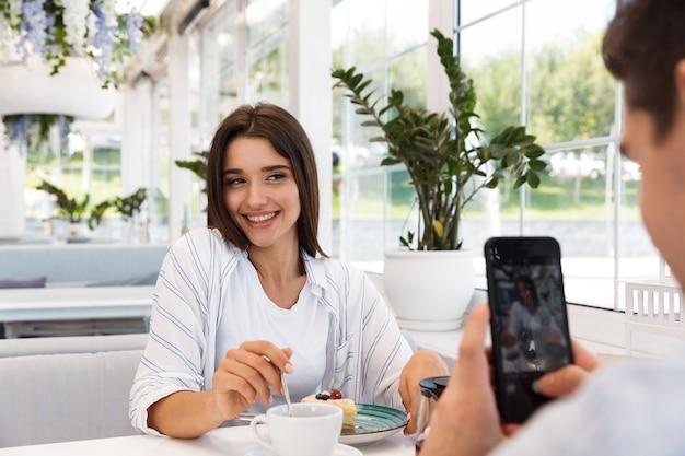 Image de l'incroyable jeune couple amoureux assis au café, manger des desserts et boire du thé. l'homme prend une photo par téléphone de sa petite amie.