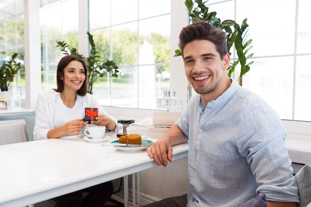 Image de l'incroyable jeune couple amoureux assis au café, manger des desserts et boire du thé. homme regardant tandis que sa petite amie la regarde présent.