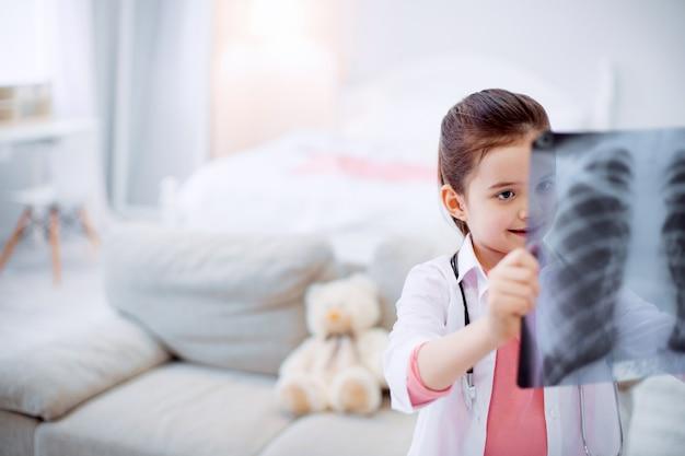 Image intéressante. happy happy jolly girl debout sur un arrière-plan flou tout en regardant la radiographie et la hausse