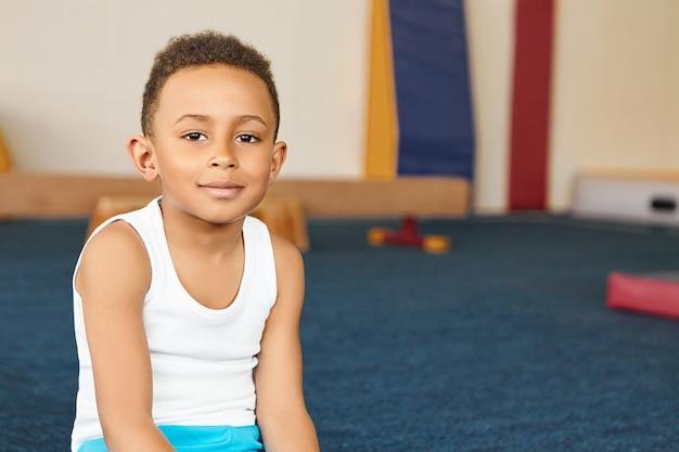 Image intérieure d'adorable écolier afro-américain positif en sportswear smiling at camera