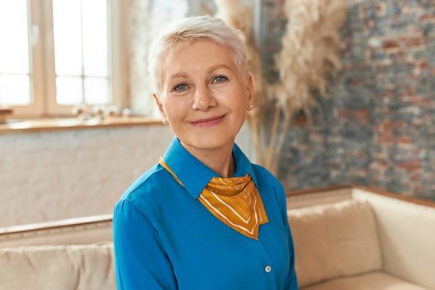 Image intérieure de la belle femme d'âge moyen portant une chemise bleue et un foulard se détendre à la maison, assis sur un canapé confortable, souriant à la caméra, ayant un regard détendu heureux.