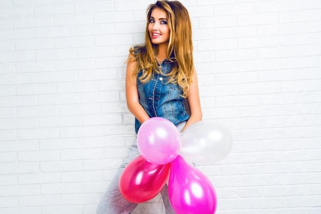 Image intérieure sur jeune femme blonde tendance hipster jouant avec des ballons roses, prêt pour la fête.