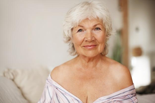 Image intérieure de jolie femme âgée de race blanche aux cheveux gris et maquillage soigné assis sur le lit vêtu d'une robe de nuit rayée, laissant les épaules nues, ayant un regard séduisant séduisant, souriant
