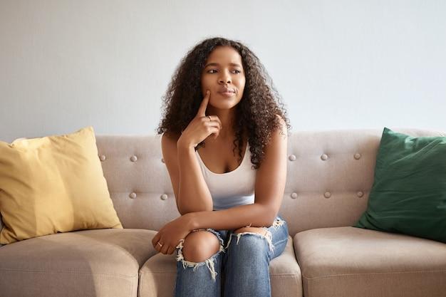 Image intérieure d'une jolie fille à la mode avec une apparence africaine assise isolée sur un canapé gris avec des coussins jaunes et verts ayant un regard réfléchi douteux, touchant le menton, disant hmm, laissez-moi réfléchir