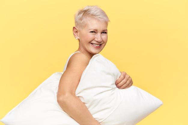 Image isolée d'heureuse belle femme à la retraite avec une coiffure de lutin portant un oreiller blanc en mousse à mémoire, va faire une sieste, souriant joyeusement.
