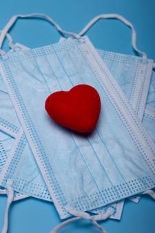 Image isolée de masques faciaux avec un coeur rouge. concept de la saint-valentin.