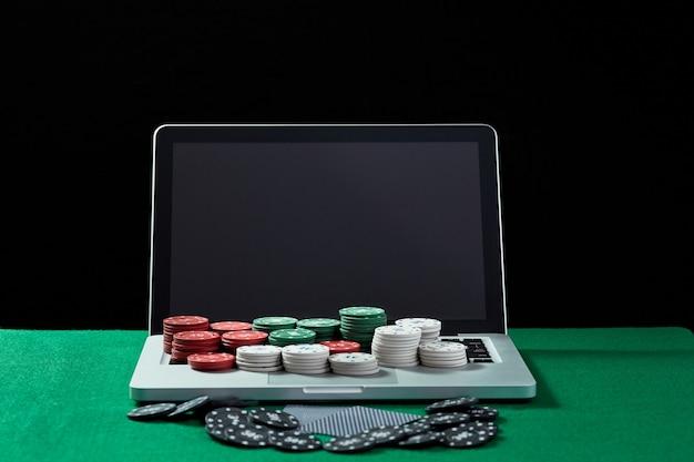 Image de jetons et de cartes de casino sur un ordinateur portable à clavier à table verte. concept de jeu en ligne, poker, casino virtuel.