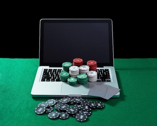 Image De Jetons Et De Cartes De Casino Sur Un Ordinateur Portable à Clavier à Table Verte. Concept De Jeu En Ligne, Poker, Casino Virtuel. Photo Premium