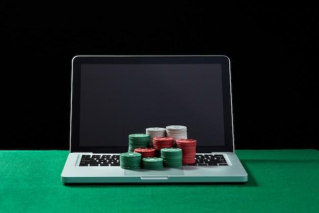 Image de jetons de casino sur un ordinateur portable à clavier à table verte. concept de jeu en ligne, poker, casino virtuel.