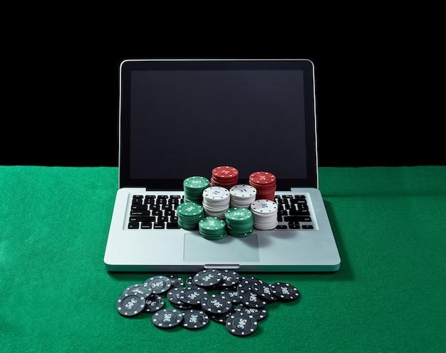 Image De Jetons De Casino Sur Un Ordinateur Portable à Clavier à Table Verte. Concept De Jeu En Ligne, Poker, Casino Virtuel. Photo Premium