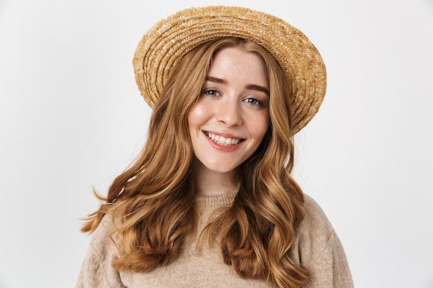 Image d'une jeune adolescente souriante et joyeuse posant isolée sur un mur blanc portant un chapeau.