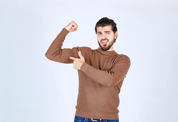 Image d'un jeune bel homme debout et montrant ses muscles. photo de haute qualité