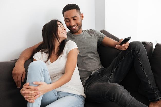 Image d'un jeune couple heureux et mignon s'embrassant et regardant la télévision sur un canapé à la maison. se regarder.