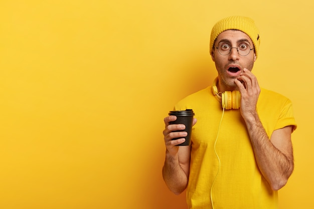 Image d'un jeune émotionnel tient une tasse de café jetable, regarde avec les yeux largement ouverts, ne peut pas en croire les yeux, porte un chapeau jaune