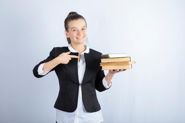 Image de jeune étudiant tenant des livres et debout sur blanc.