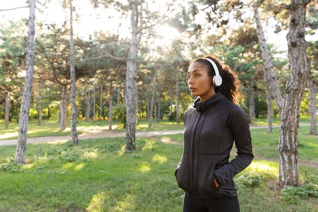 Image de la jeune femme de 20 ans portant un survêtement noir et des écouteurs, marchant dans le parc verdoyant