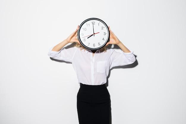 Image de jeune femme d'affaires debout isolé sur le visage de revêtement mural blanc avec horloge.