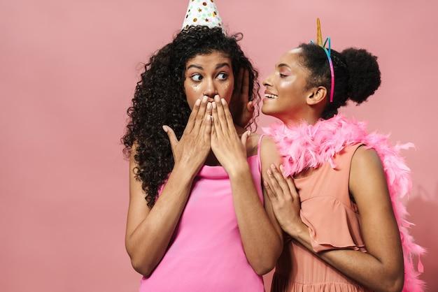 Image d'une jeune femme afro-américaine chuchotant à l'oreille de son ami