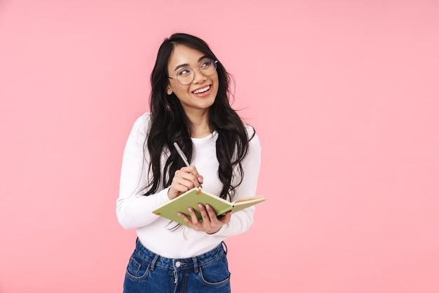 Image d'une jeune femme asiatique brune portant des lunettes prenant des notes dans un livre de journal isolé sur rose