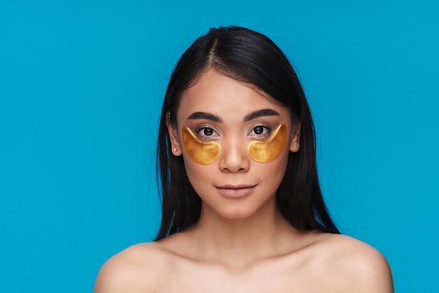 Image d'une jeune femme asiatique posant isolée sur un mur bleu prendre soin de la peau sous les yeux avec des patchs.