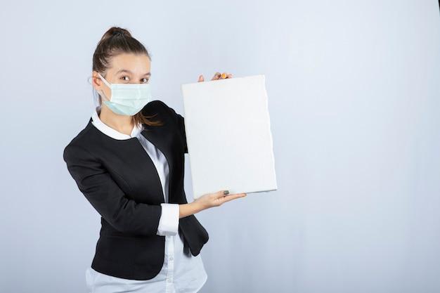 Image de la jeune femme au masque facial gardant une toile vierge sur un mur blanc. photo de haute qualité