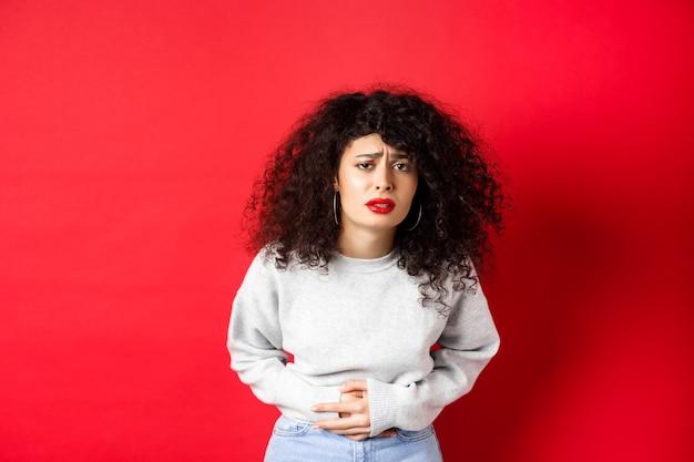 Image d'une jeune femme ayant des maux d'estomac, se pliant de douleur et se plaignant de crampes menstruelles douloureuses, debout sur fond rouge