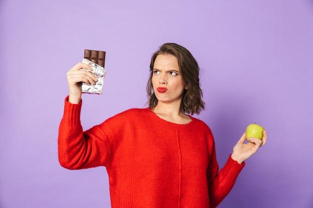 Image d'une jeune femme confuse posant isolé sur mur violet tenant le chocolat et la pomme.