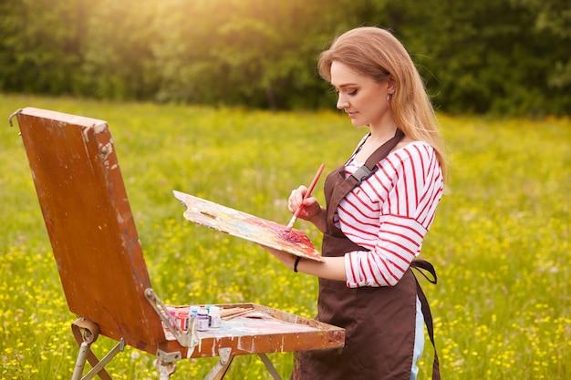 Image de jeune femme dessinant une image sur toile, à l'aide d'un carnet de croquis pour dessiner dans la nature, profil de peintre avec pinceau et palette de peintures de travail inspirées du paysage de prairie. concept de style de vie