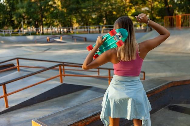 Image de jeune femme élégante patineuse avec cruiser board sur skate aire de jeux