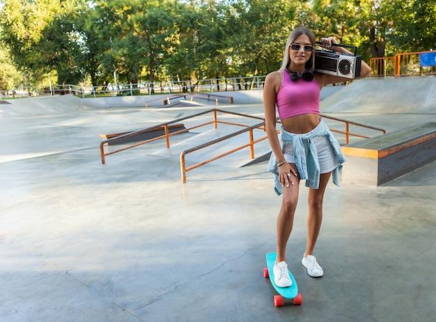 Image d'une jeune femme élégante patineuse avec planche de croisière et magnétophone rétro boombox dans skatepark