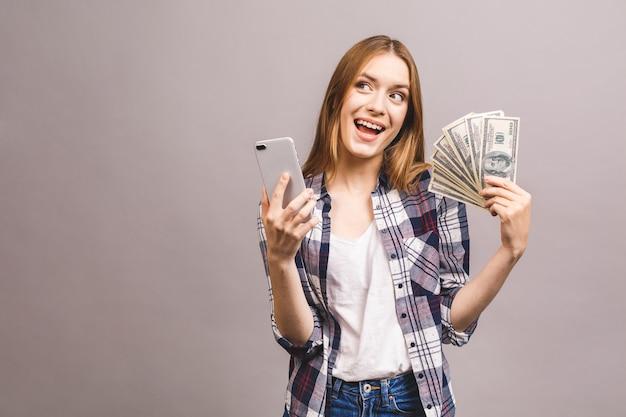 Image de jeune femme excitée. étonné avec un téléphone mobile, tenant de l'argent.