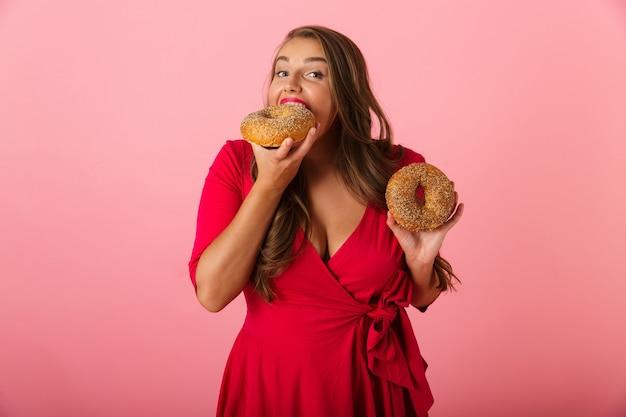 Image d'une jeune femme excitée isolée sur un mur rose manger des beignets.
