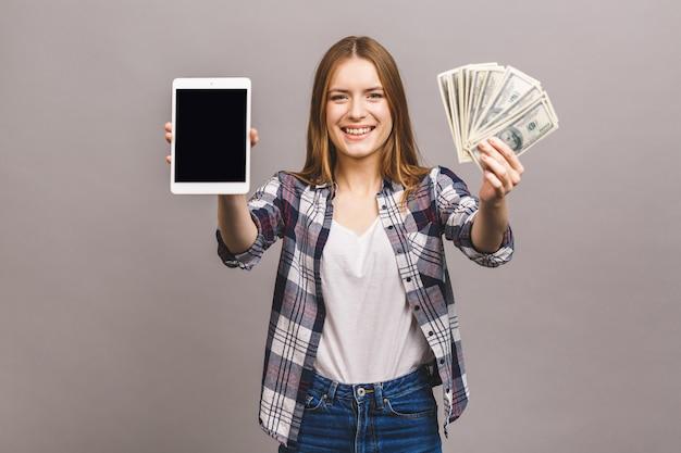Image de jeune femme excitée. à la recherche de l'appareil photo montrant l'affichage de l'ordinateur tablette contenant de l'argent.