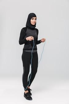 Image de jeune femme fitness musulman posant isolé faire des exercices avec corde à sauter.