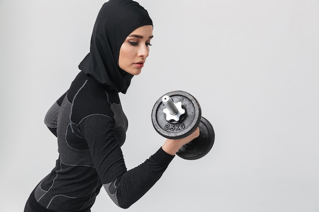 Image de jeune femme fitness musulman posant isolé faire des exercices avec haltère.