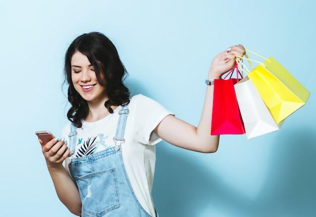 Image d'une jeune femme gaie montrant un téléphone mobile à écran blanc tout en portant des sacs à provisions isolés sur un mur jaune