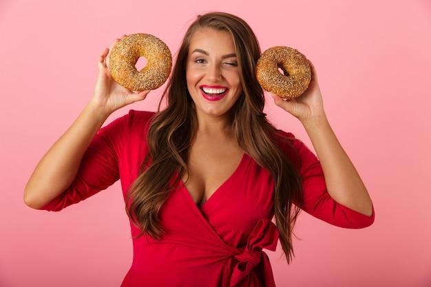Image d'une jeune femme heureuse isolée sur mur rose tenant des beignets.