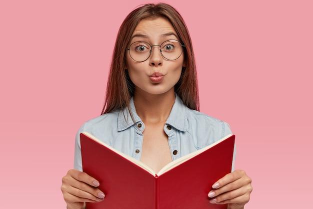 Image de jeune femme à la recherche agréable fait la moue des lèvres