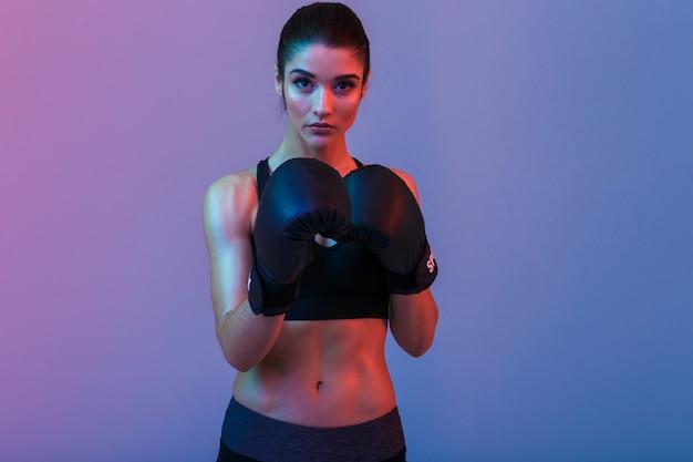 Image de jeune femme sportive en survêtement et gants de boxe noirs combats dans une salle de sport, isolé sur mur violet