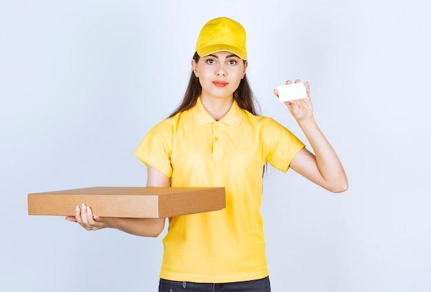 Image d'une jeune femme tenant un paquet et montrant une carte de visite.
