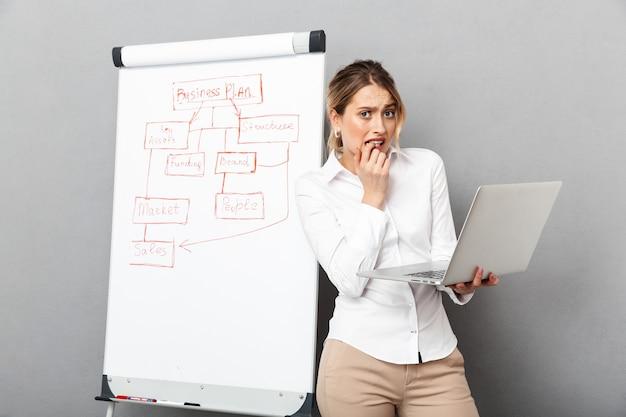 Image de jeune femme en tenue de soirée à l'aide de flipchart et ordinateur portable tout en faisant la présentation au bureau, isolé