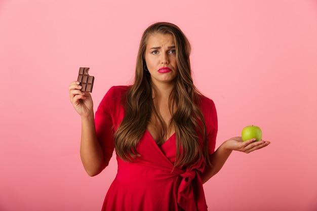 Image d'une jeune femme triste isolée sur un mur rose tenant du chocolat et de la pomme.