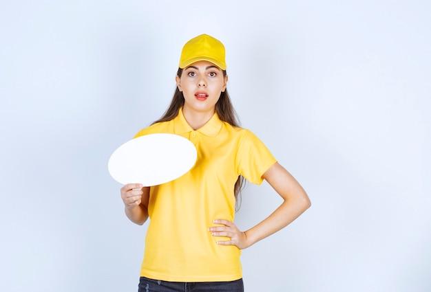 Image de jeune femme en uniforme jaune posant avec une bulle de dialogue vide.