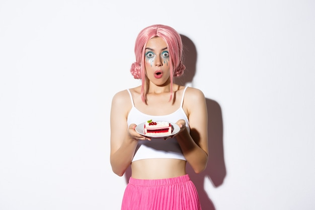 Image d'une jeune fille d'anniversaire surprise en perruque rose, tenant un gâteau sur une assiette et regardant la caméra émerveillée, debout sur fond blanc.