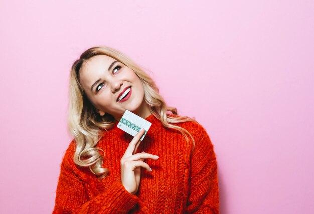 Image d'une jeune fille blonde tenant une carte de crédit et souriant dans la chambre sur un mur rose