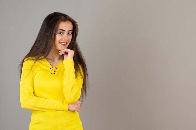 Image de jeune fille en haut jaune debout et posant sur un mur gris.