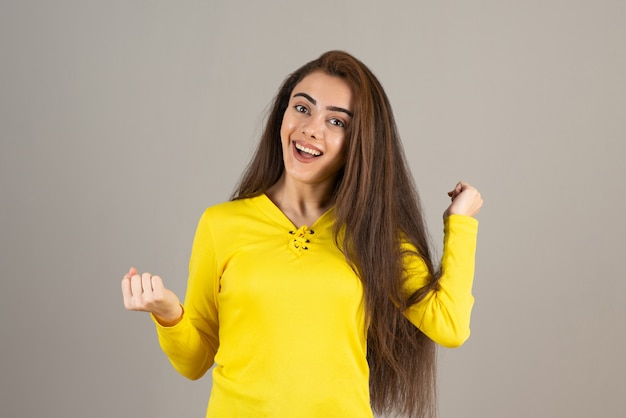Image de jeune fille en haut jaune posant sur un mur gris.