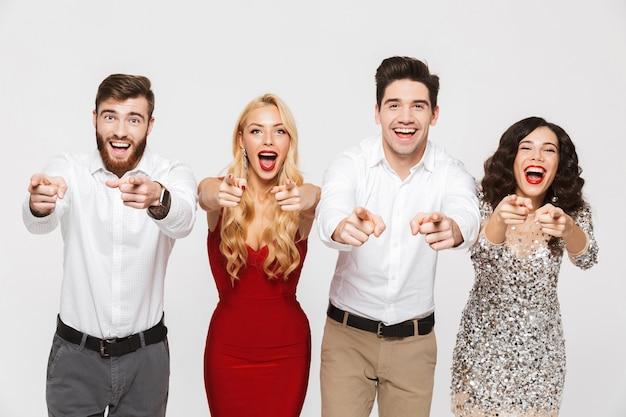 Image d'un jeune groupe d'amis excité choqué debout isolé sur blanc pointant vers vous.