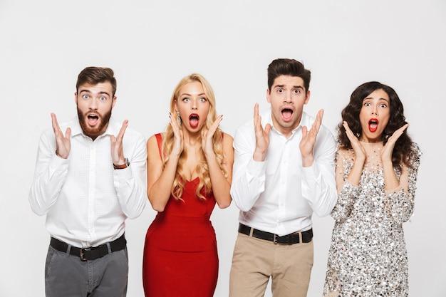 Image d'un jeune groupe d'amis excité choqué debout isolé sur blanc.